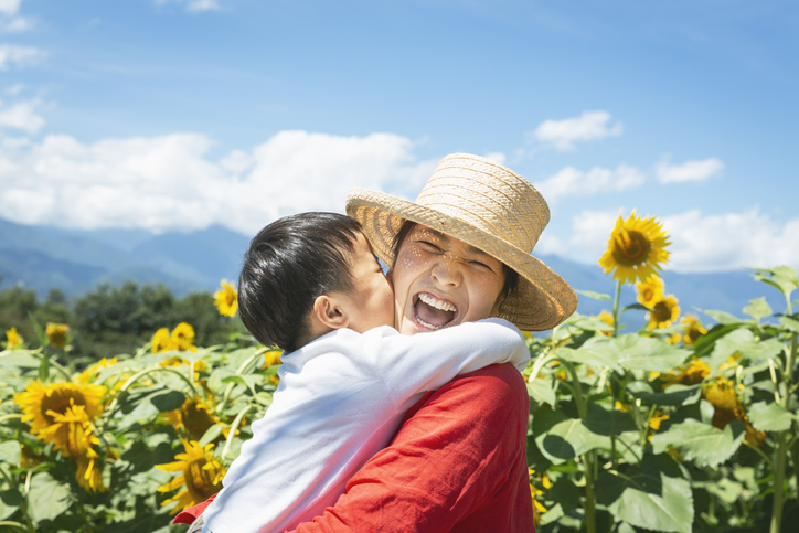 Mother and son relaxed in the sun flower fields